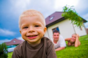 Happy child in front of the house with parents in the background